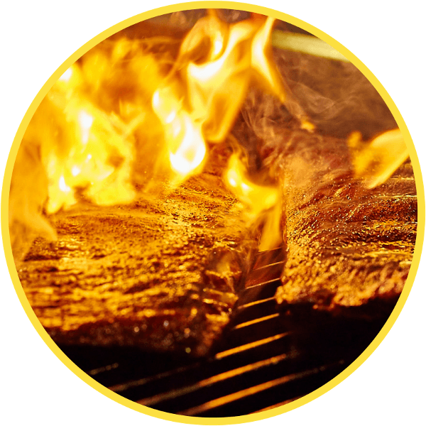 Ribs Sizzling on a Grill with Flames